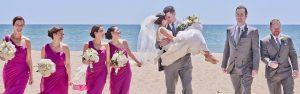Bryllup på en strand, der brud og brudgom har flere forlovere hver seg.