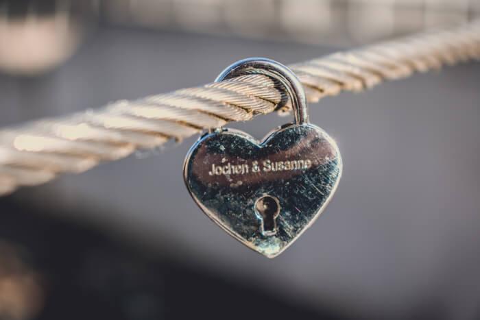 Hengelås i stål som er formet som et hjerte. Låsen henger på en stålvaier.