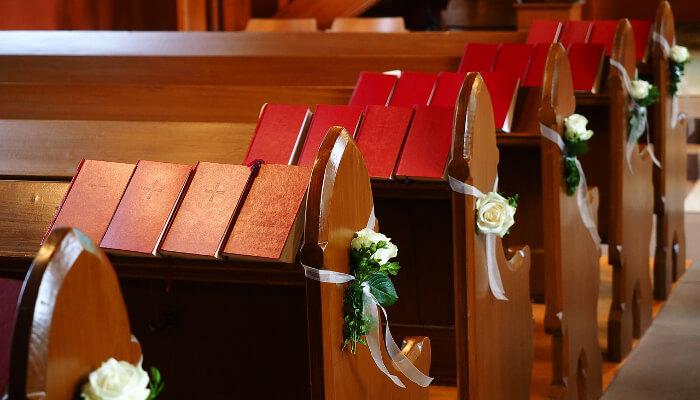 Salmebøker som er plassert ut på benkene i en kirke som er pyntet for bryllup.