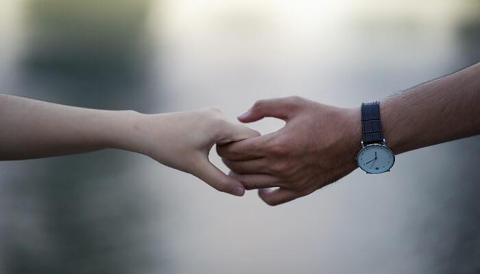 En dame og en mann som holder hendene til hverandre.